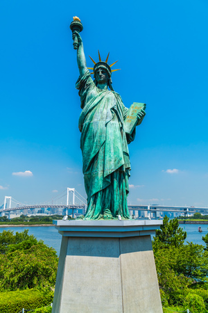 Liberty statue with rainbow bridge in odaiba island tokyo japan