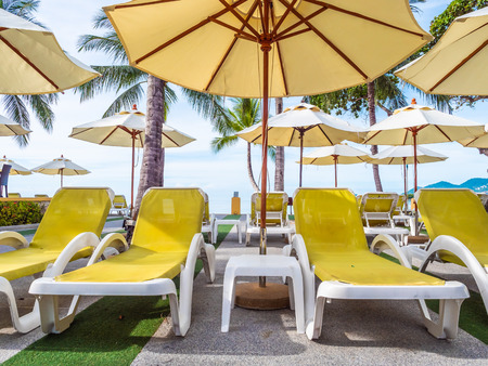 Umbrella and chair around luxury outdoor swimming pool in hotel and resort for vacation and travel
