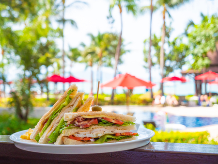 Sandwich for breakfast in white plate with outdoor swimming pool view in hotel and resort Stockfoto