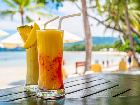 Iced drinking smoothies glass on wooden table with sea and ocean view for relax