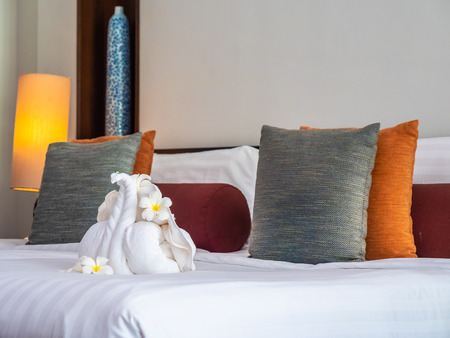 White elephant towel and comfortable pillow on bed decoration in hotel bedroom interior Reklamní fotografie - 122621392