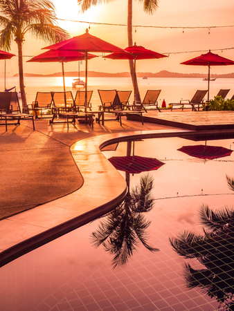 Umbrella and chair around outdoor swimming pool in hotel and resort at sunrise time