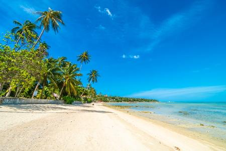 Beautiful tropical beach sea and sand with coconut palm tree on blue sky and white cloud for travel and vacation Imagens