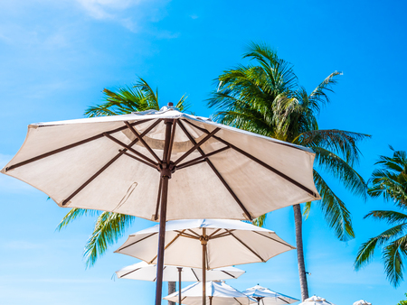 White umbrella with coconut palm tree with sea ocean on blue sky background for travel and vacation Imagens - 115496185