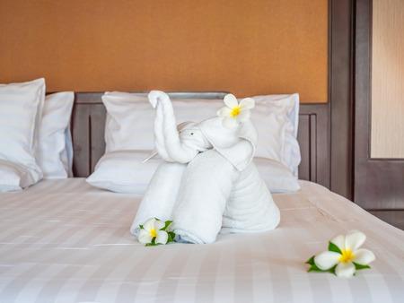 White elephant towel and comfortable pillow on bed decoration in hotel bedroom interior