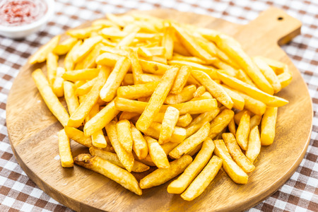 French fries on wooden plate with tomato or ketchup sauce - Junk or Unhealthy food style Imagens - 115468545