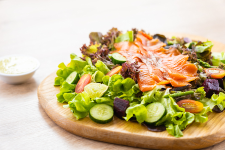 Raw Smoked salmon meat fish with fresh green vegetable salad and sauce - Healthy food concept Imagens - 115468555