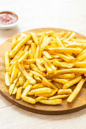 French fries on wooden plate with tomato or ketchup sauce - Junk or Unhealthy food style Imagens - 115468560