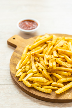 French fries on wooden plate with tomato or ketchup sauce - Junk or Unhealthy food style Imagens - 115468565