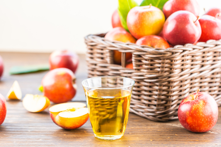 Apples juice in glass with red apple in the basket - Healthy food and drinking concept Imagens - 115468542