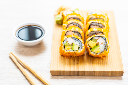 California maki rolls sushi on wooden plate with sauce and chopsticks - Japanese food style Imagens - 115468459