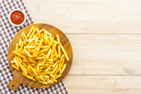 French fries on wooden plate with tomato or ketchup sauce - Junk or Unhealthy food style Imagens - 115468469