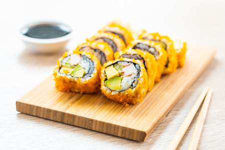 California maki rolls sushi on wooden plate with sauce and chopsticks - Japanese food style Imagens - 115468297