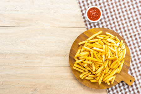 French fries on wooden plate with tomato or ketchup sauce - Junk or Unhealthy food style Imagens - 115468299