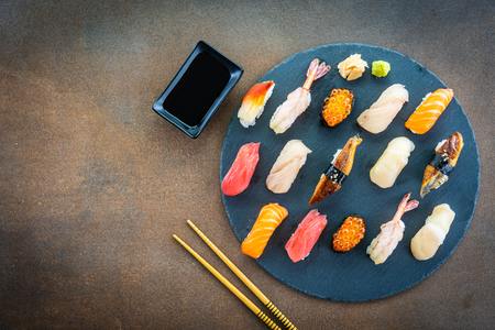 Nigiri sushi set with salmon tuna fish shrimp prawn eel shell and other sashimi on black slate - Japansese food style