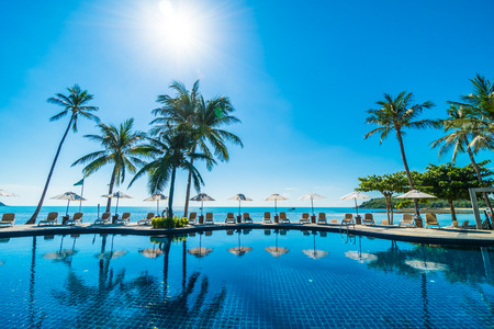 Beautiful tropical beach and sea with umbrella and chair around swimming pool in hotel resort for travel and vacation Standard-Bild - 114960101