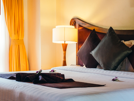 Comfortable pillow on bed with light lamp decoration in hotel bedroom Archivio Fotografico