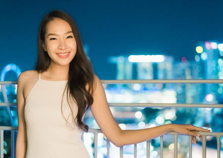 Beautiful Asian women smile and happy with singapore city view at night