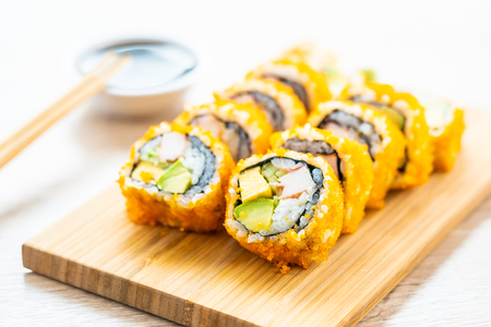 California maki rolls sushi on wooden plate with sauce and chopsticks - Japanese food style