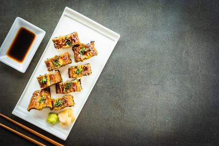 Anguille grillée ou poisson unagi avec du saumon et des légumes à l'intérieur d'un rouleau de sushi maki et d'une sauce sucrée sur une assiette blanche - style de cuisine japonaise