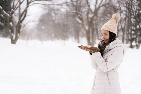 Beautiful young asian woman smiling happy with travel in snow winter season at Hokkaido Japan Sajtókép