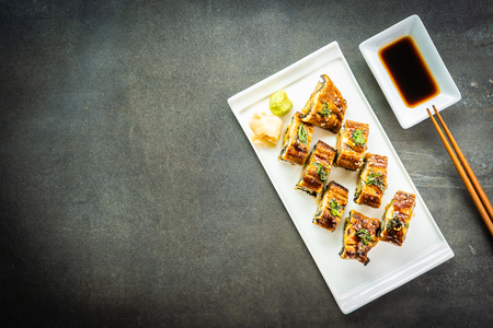 Grilled eel or unagi fish with salmon and vegetable inside sushi maki roll and sweet sauce on white plate - Japanese food style Reklamní fotografie