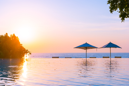 Beautiful landscape outdoor swimming pool with umbrella and deck chair in hotel resort for relax travel and vacation at sunrise or sunset time