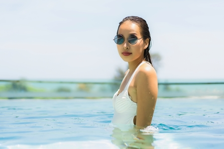 Beautiful young asian woman happy and smile in swimming pool for relax travel and vacation concept Stock Photo