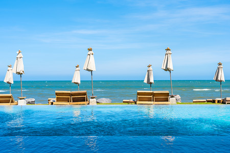 Beautiful outdoor nature landscape with bed deck chair around swimming pool in hotel resort on blue sky background for travel and vacation concept Banque d'images