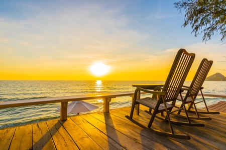 Chaise et table en bois vides sur le patio extérieur avec une belle plage tropicale et la mer au fond du lever ou du coucher du soleil pour les vacances et les voyages