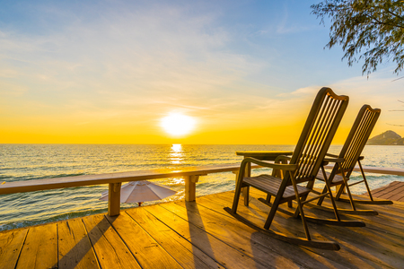Empty wood chair and table at outdoor patio with beautiful tropical beach and sea at sunrise or sunset background for vacation and travel
