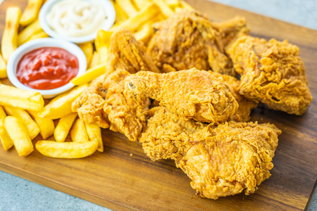 Fried chicken wings with french fries and tomato or ketchup and mayonnaise sauce on wood cutting board - Junk or Unhealthy food style