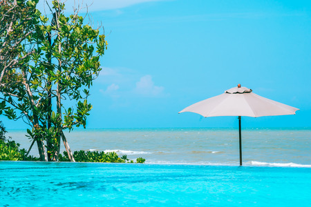 Umbrella and chair around swimming pool neary beautiful landscape of sea ocean beach with blue sky and white cloud for leisure travel and vacation Imagens