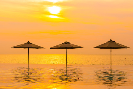 Umbrella and chair around swimming pool neary sea ocean beach at sunrise or sunset time for leisure travel and vacation Imagens