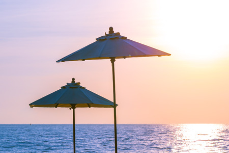 Umbrella and chair around swimming pool for leisure travel and vacation nearby sea ocean beach at sunset or sunrise time Imagens