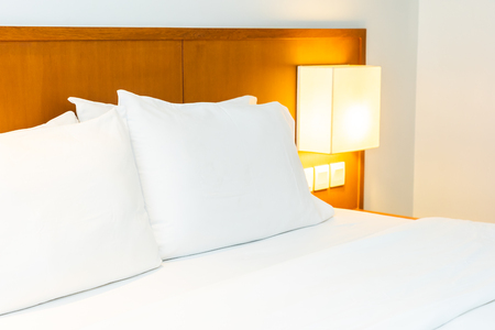White comfortable pillow on bed with light lamp decoration in bedroom interior Imagens