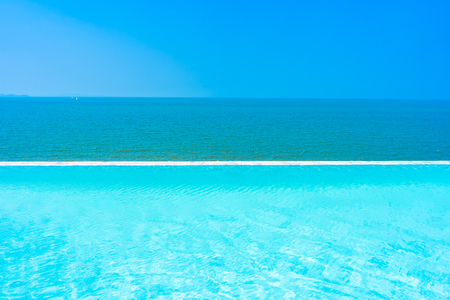 Beautiful landscape of sea ocean with outdoor swimming pool on white cloud blue sky background for leisure travel and vacation