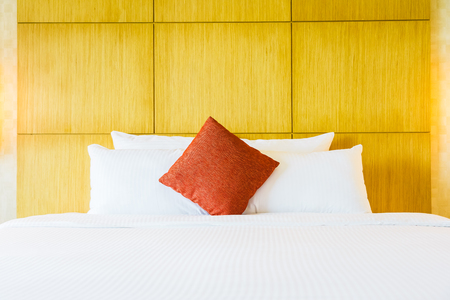 White comfortable pillow on bed decoration in hotel bed room interior Imagens