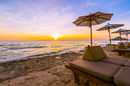 Umbrella and chair with pillow around beautiful landscape of beach and sea at sunrise or sunset time for holiday vacation and travel Imagens