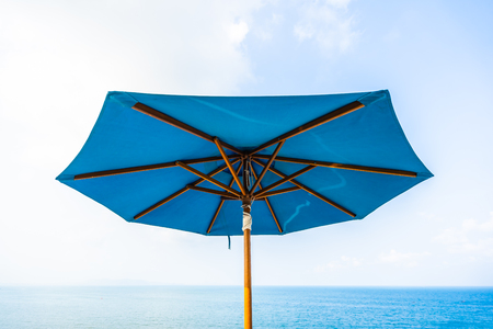 Blue color of umbrella with cloud sky and sea ocean for leisure travel and vacation Imagens