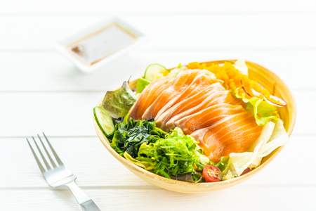 Raw fresh salmon fish meat sashimi with vegetables salad and sauce - Japanese and Healthy food concept Imagens