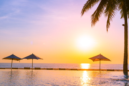 Beautiful landscape outdoor swimming pool with umbrella and deck chair relax travel and vacation at sunrise or sunset time