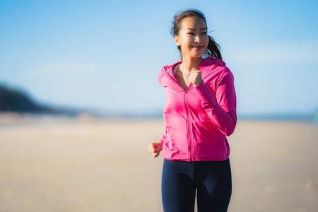 Porträt schöne junge asiatische frau, die auf der tropischen naturlandschaft des strandmeeres für ein gesundes konzept läuft oder trainiert Standard-Bild