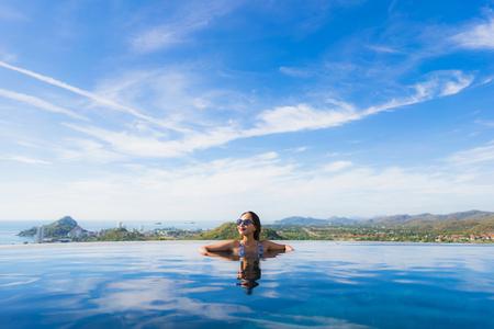 Portrait schöne junge asiatische Frau Lächeln glücklich entspannen um Schwimmbad im Hotelresort für Freizeitreisen und Urlaubskonzepte