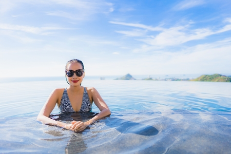 Portrait beautiful young asian woman smile happy relax around swimming pool in hotel resort for leisure travel and vacation concept Banco de Imagens