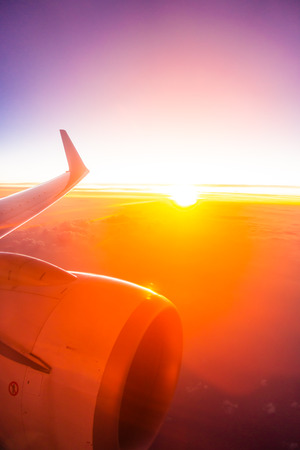 Beautiful aerial view from airplane wing on white cloud and sky at sunset or sunrise time