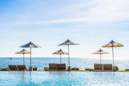 Beautiful landscape of sea ocean on sky with umbrella and chair around luxury outdoor swimming pool  for leisure travel and vacation