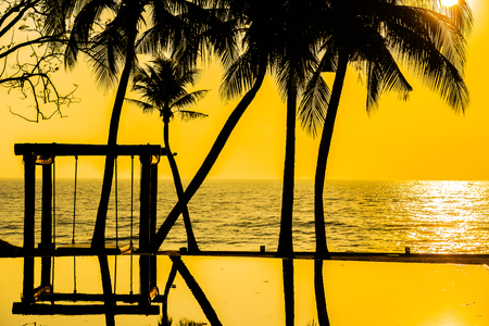Beautiful Silhouette coconut palm tree on sky around swimming pool nearby sea ocean beach at sunset or sunrise time for leisure travel and vacation concept