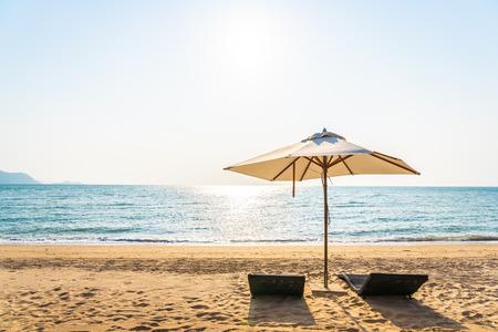 Sonnenschirm und Lounge am schönen Strand Meer Ozean am Himmel für Freizeitreisen und Urlaubskonzept