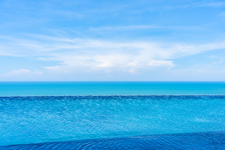 Beautiful outdoor landscape of infinity swimming pool in hotel resort with sea ocean on white cloud blue sky view for leisure travel in holiday vacation 免版税图像